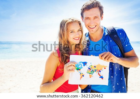 couple holding a map with travel destinations - stock photo