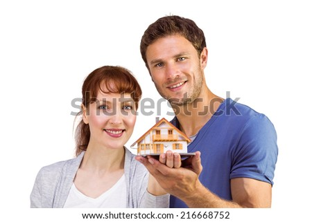 Couple holding a model house together on a white background - stock photo