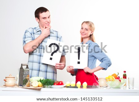 couple holding a plate with signs question and exclamation - stock photo