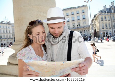 Couple holding a touristic map of Bordeaux - stock photo