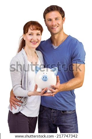 Couple holding a white piggy bank on a white background - stock photo