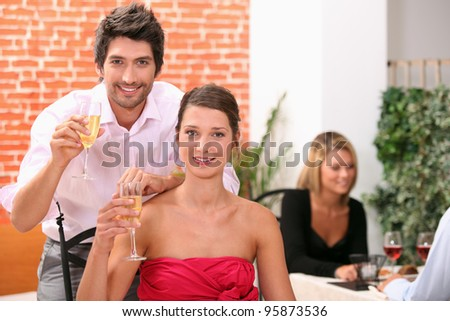 Couple holding champagne flutes in restaurant - stock photo