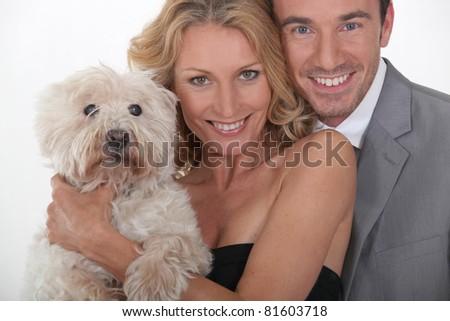 Couple holding dog. - stock photo