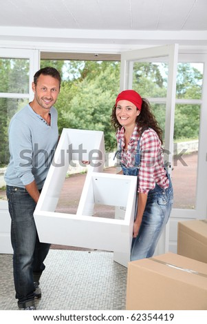 Couple holding furniture in their new home