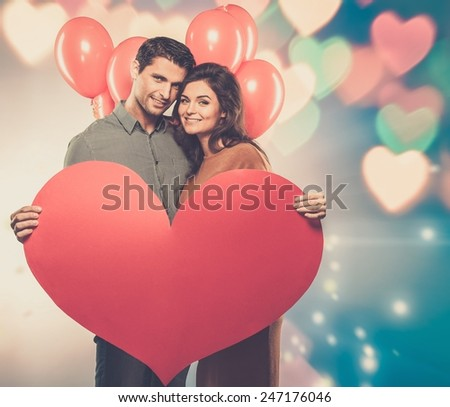 Couple holding handmade paper heart and red balloons  - stock photo