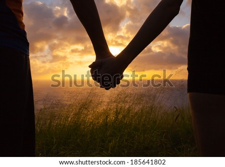 Couple holding hands a watching a beautiful sunset in Hawaii. - stock photo