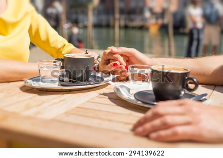 Couple holding hands and drinking coffee in cafe outdoors - stock photo