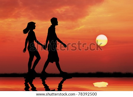 couple holding hands and walking during sunset - stock photo