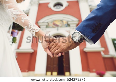 couple holding hands at church entrance