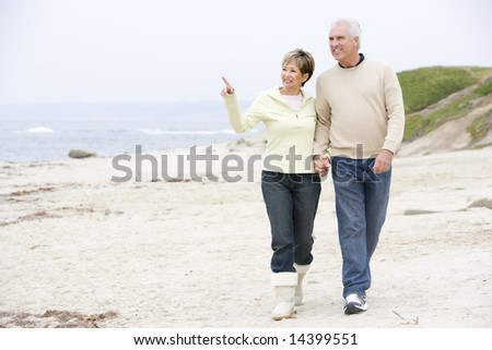 Couple holding hands at the beach smiling and pointing - stock photo