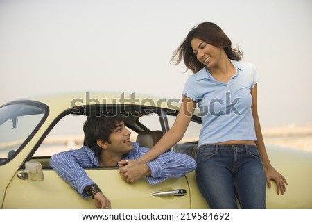 Couple holding hands by car - stock photo