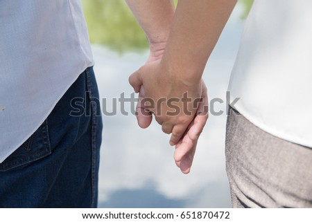 Couple holding hands in garden