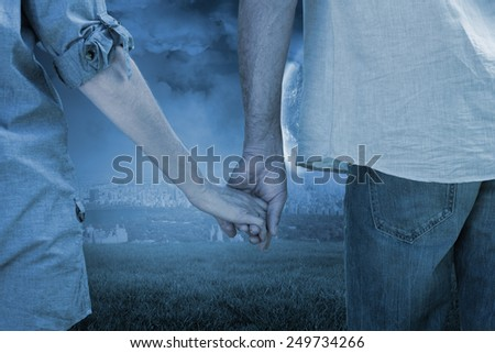 Couple holding hands in park against large moon over city - stock photo