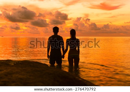Couple holding hands in the water while watching the sunset. - stock photo
