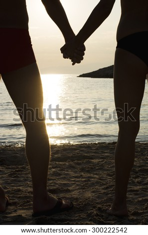 Couple holding hands on a beach at sunset, silhouette effect.