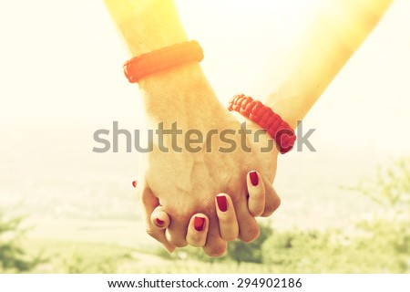 Couple holding hands on a sunny day - stock photo