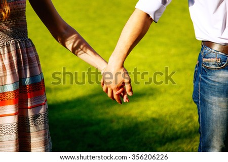 Couple holding hands on the background of green grass - stock photo