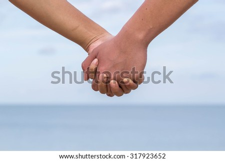 Couple holding hands on the beach.