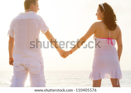 Couple holding hands together on the beach at sunrise - stock photo