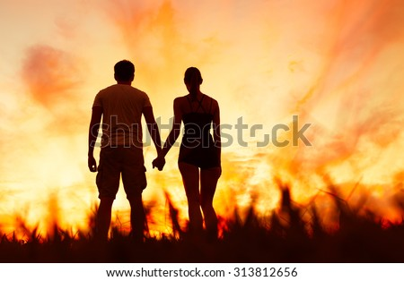 Couple holding hands while watching the sunset.  - stock photo