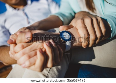Couple  holding hands with white watches in sunny day. - stock photo