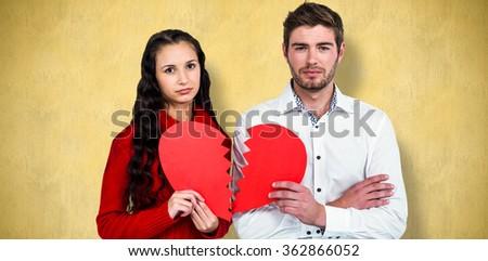 Couple holding heart halves against orange background - stock photo