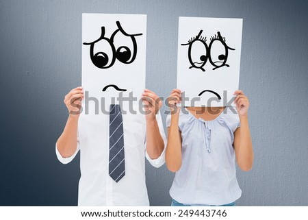 Couple holding paper over their faces against digitally generated grey vignette background - stock photo