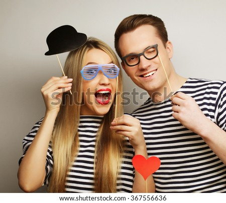 couple holding party glasses and hat on sticks - stock photo