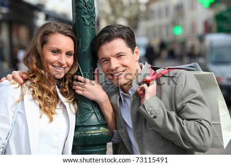 Couple holding shopping bags in town - stock photo