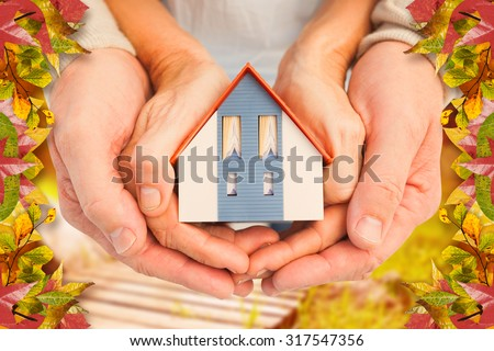 Couple holding small model house in hands against autumn scene - stock photo