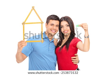 Couple holding tape measure in form of house and key isolated on white background