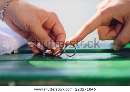 couple holding their wedding rings - stock photo