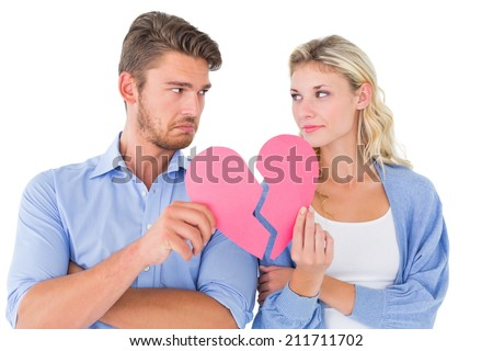 Couple holding two halves of broken heart on white background - stock photo