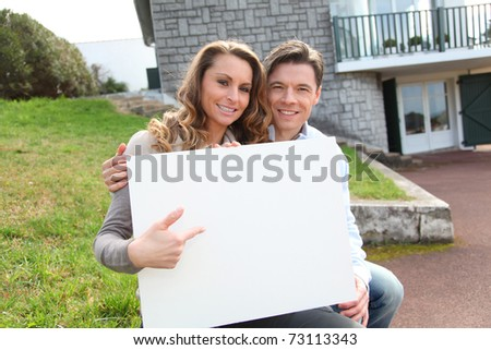 Couple holding whiteboard in front of their house - stock photo