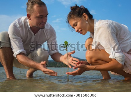 Couple holding young plant in hands