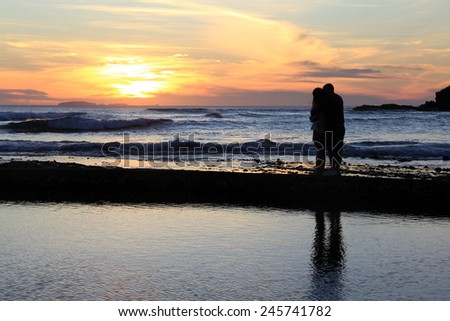 couple hugging and watching the sunset.  - stock photo