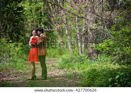 Couple hugging at forest with spring branches. Stylish man at velvet jacket and girl in red dress in love together