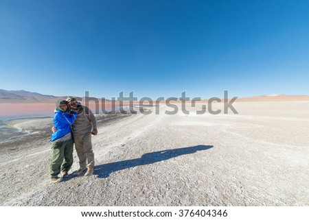 Couple hugging at Laguna Colorada with expansive view on barren mountain range and high altitude desert on the highlands of the Andes on the way to the famous Uyuni Salt Flat, Bolivia. - stock photo