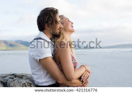 Couple hugging by the sea. Young couple at the beach holding each other. Boyfriend embracing girl from behind at beach during sunset at seashore. - stock photo