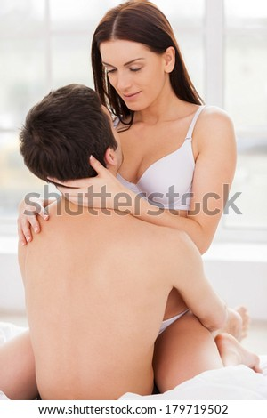Couple hugging in bed. Beautiful young loving couple in underwear hugging while sitting in bed - stock photo