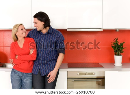 Couple hugging in kitchen - stock photo
