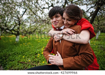 Couple hugging in love near blooming trees garden. Stylish man at velvet jacket and girl in red dress in love together