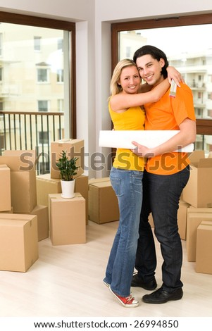 Couple hugging in new house - stock photo