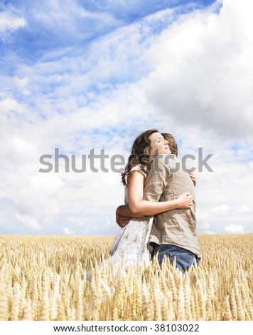 Couple hugging in the middle of a wheat field - stock photo