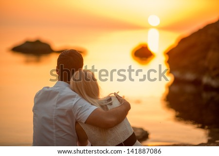couple hugging on the beach on sunrise - stock photo