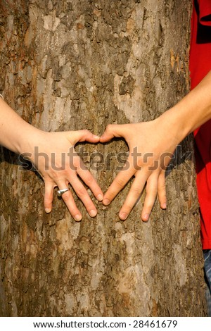 Couple hugging tree and making a heart.
