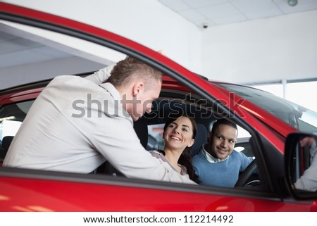Couple in a car listening to a salesman in a car shop