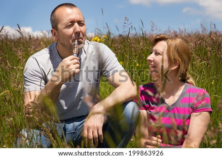 couple in a meadow with electric cigarette