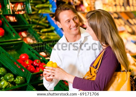 Couple in a supermarket at the vegetable shelf shopping for groceries, they are checking out the groceries