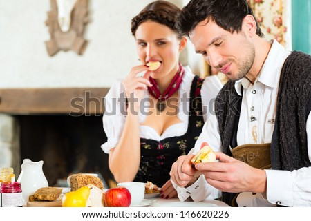 Couple in a traditional mountain hut having a meal